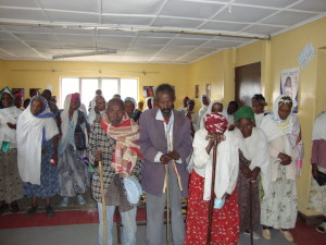 Elderly at prayer before their food programme